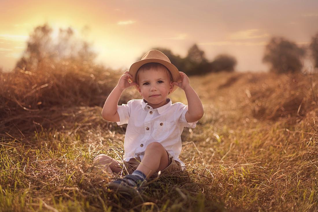 süßer Junge auf Feld mit strohhut bei Sonenuntergang