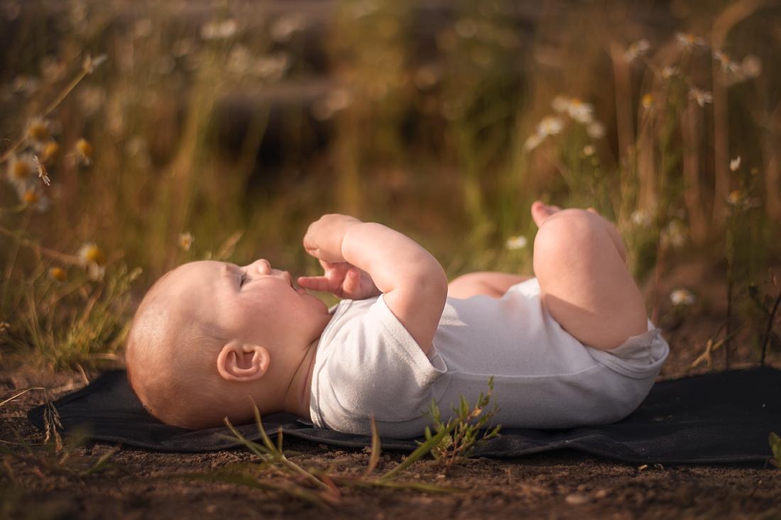 5 Monate altes Baby liegt auf Decke