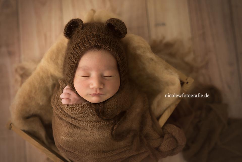 süßes Babyfoto eines Neugeborenen das in einer Holzbox liegt und eine Teddymütze trägt.